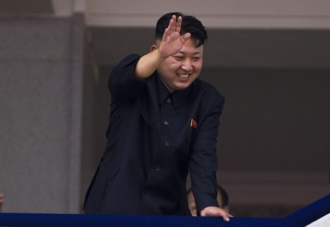 FILE - In this July 27, 2013 file photo, North Korean leader Kim Jong Un leans over a balcony and waves to Korean War veterans cheering below at the end of a mass military parade on Kim Il Sung Square in Pyongyang to mark the 60th anniversary of the Korean War armistice. North Korea is warning that the release of a new American comedy about a plot to assassinate leader Kim Jong Un would be an