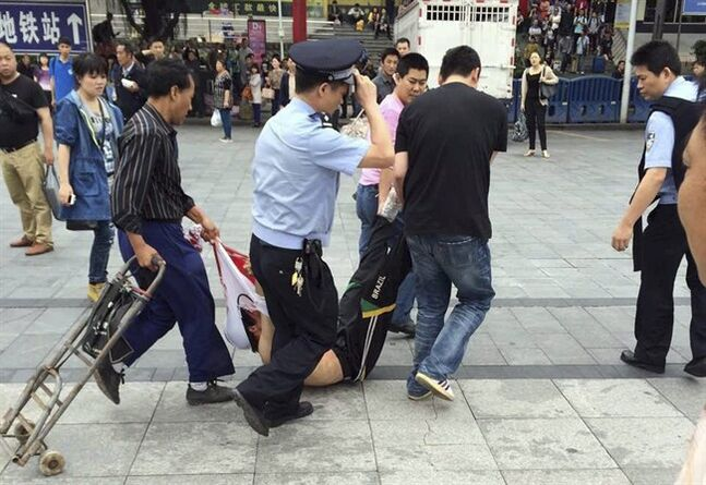 In this photo taken by a mobile phone, a suspected assailant is taken away after being subdued in an attack at a railway station in Guangzhou in south China's Guangdong province Tuesday May 6, 2014. The hacking attack Tuesday at the busy railway station in southern China left six people injured, police said, in the third high-profile attack on civilians at a train station in a little more than two months. (AP Photo) CHINA OUT
