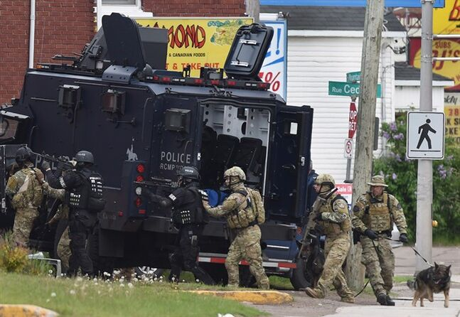 Emergency response officers enter a residence in Moncton, N.B. on Thursday, June 5, 2014. The two RCMP officers in New Brunswick who were wounded in shootings last month that also killed three of their colleagues are expressing gratitude for the public's support THE CANADIAN PRESS/Andrew Vaughan