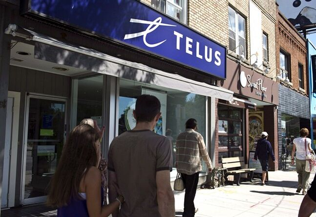 Pedestrians walk by a Telus store in Toronto, on August 15, 2013. THE CANADIAN PRESS/Galit Rodan