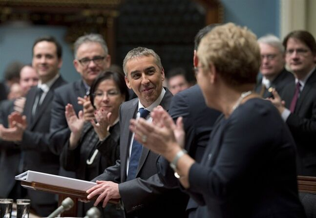 Quebec Finance Minister Nicolas Marceau is applauded by members of the government as he stands to present his budget speech, Thursday, February 20, 2014 at the legislature in Quebec City. THE CANADIAN PRESS/Jacques Boissinot