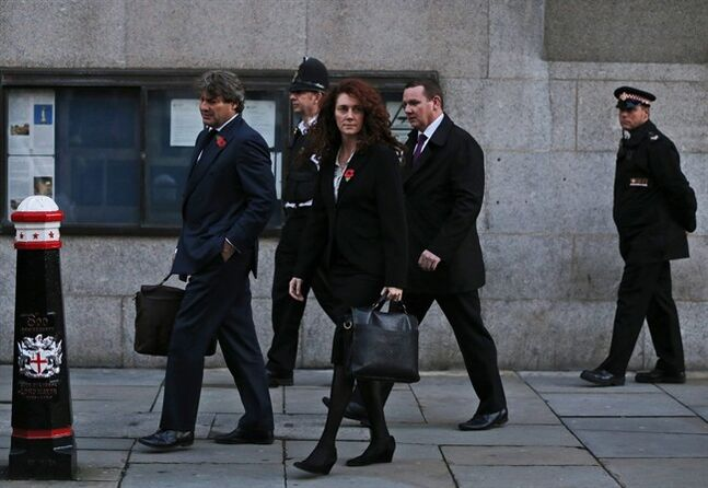 FILE - In this Monday, Oct. 28, 2013, file photo, former News of the World national newspaper editor Rebekah Brooks, accompanied by her husband, Charlie Brooks, left, leaves the Central Criminal Court in London. Almost four months into her trial, Rebekah Brooks is finally getting her day in court. After watching in silence from the dock as her alleged crimes were dissected, the 45-year-old former newspaper editor, once Rupert Murdoch's top British lieutenant, is expected to take the stand to rebut charges of phone hacking, bribery and obstructing a police investigation. The defense case in Britain's hacking trial is scheduled to open Wednesday, Feb. 19, 2014, beginning with Brooks _ the first name on the indictment _ before moving on to six other defendants. All deny charges of wrongdoing at the News of the World and Sun tabloids. (AP Photo/Lefteris Pitarakis, File)