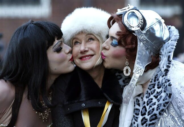 Actress Helen Mirren is kissed by drag actors Tony Oblen, left, and Ethan Hardy, right, as she is honored as woman of the year by Harvard University's Hasty Pudding Theatricals in Cambridge, Mass., Thursday, Jan. 30, 2014. (AP Photo)