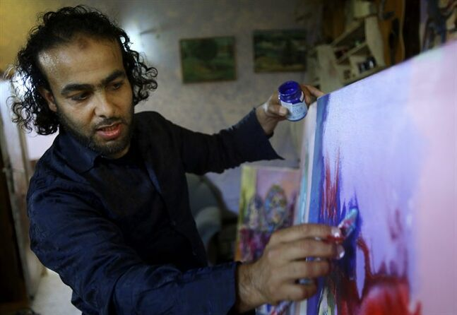 In this photo taken Wednesday, May 14, 2014, Palestinian artist Ismail Dahlan, 36, paints at his studio in Beit Lahiya, in the northern Gaza Strip, Wednesday, May 14, 2014. Dahlan is among 45 Gaza artists showing their work in a West Bank exhibit, a rare showcase for painters living in the Hamas-ruled territory that is largely sealed off by an Israeli-Egyptian border blockade. (AP Photo/Adel Hana)