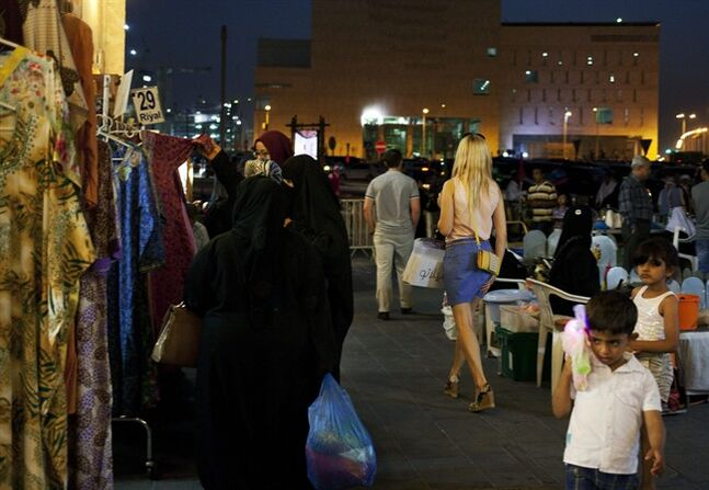 "In this Monday, June 2, 2014 photo, a foreign woman wearing a short dress walks at Souq Waqif in Doha, Qatar. A number of Qatari women are aiming to raise awareness with a campaign called ""Reflect Your Respect"