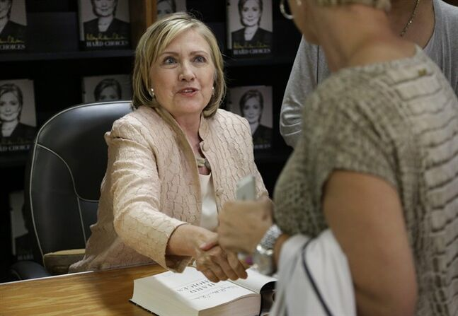 Former Secretary of State Hillary Rodham Clinton shakes hands with a customer at Bunch of Grapes Bookstore, in Vineyard Haven, Mass., on the island of Martha's Vineyard, Wednesday, Aug. 13, 2014, during a book signing event for her memoir
