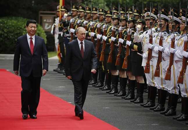 Russia's President Vladimir Putin, center, and China's President Xi Jinping, left, review an honor guard during a welcoming ceremony at the Xijiao State Guesthouse ahead of the fourth Conference on Interaction and Confidence Building Measures in Asia (CICA) summit, in Shanghai, China Tuesday, May 20, 2014. (AP Photo/Carlos Barria, Pool)