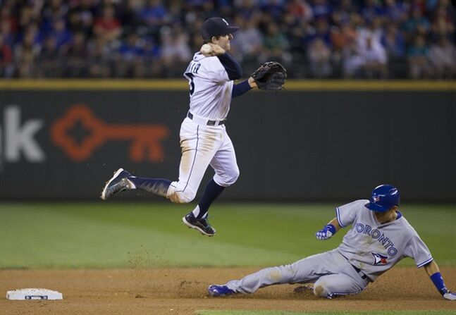 Seattle Mariners shortstop Brad Miller, left, tries to turn a double play as Toronto Blue Jays' Munenori Kawasaki slides into second base during the seventh inning of a baseball game, Wednesday, Aug. 13, 2014, in Seattle. Kawasaki was out at second and Miller was not able to complete the double play. (AP Photo/Stephen Brashear)