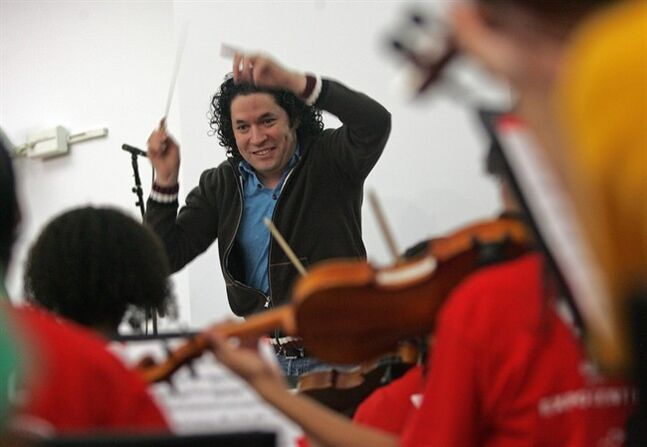 FILE - In this Oct. 29, 2011 file photo, conductor Gustavo Dudamel rehearses the Youth Orchestra of Los Angeles at YOLA EXPO Center Chamber Orchestra in Choral Hall at Walt Disney Concert Hall in Los Angeles. Dudamel is facing the heat in his native Venezuela for not speaking out against embattled President Nicolas Maduro while holding a series of high-profile concerts in Caracas, Venezuela in February 2014. (AP Photo/Ringo H.W. Chiu, File)