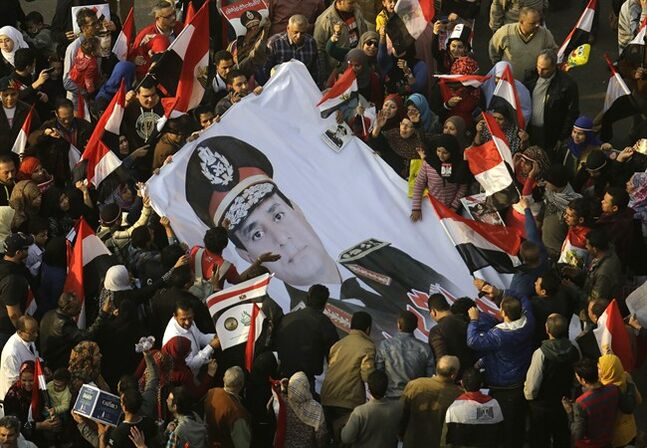 FILE -- In this Saturday, Jan. 25, 2014 file photo, Egyptians wave a giant poster of Egypt's Defense Minister, Gen. Abdel-Fattah el-Sissi in Tahrir Square, in Cairo, Egypt. Egypt's likely next president, retired military chief Abdel-Fattah el-Sissi, says ties with the West and the United States will improve after elections May 26-27, 2014, confident that a strong show of public support will prove that Egyptians wanted his ouster of the country's Islamist president, which threw relations between the two allies into their worst strains ever. (AP Photo/Amr Nabil, File)