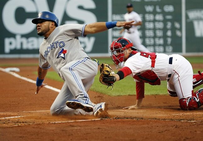 Toronto Blue Jays' Melky Cabrera slides safely into home past Boston Red Sox catcher Christian Vazquez as he scores on a fielder's choice grounder by Juan Francisco in the first inning of a baseball game at Fenway Park in Boston, Wednesday, July 30, 2014. (AP Photo/Elise Amendola)