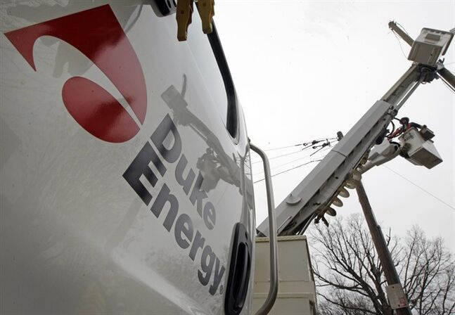 FILE - In this Feb. 14, 2012 file photo, Duke Energy employees work on power lines in Charlotte, N.C. Duke Energy Corp. reports quarterly earnings on Tuesday, Feb. 18, 2014. (AP Photo/Chuck Burton, File)