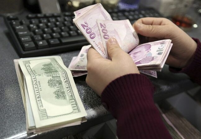 FILE - In this file photo taken Tuesday, Jan. 28, 2014, a woman counts U.S. dollar and Turkish lira banknotes at a currency exchange office in Istanbul, Turkey. From India to Indonesia, investors are finding something to like about stocks in emerging markets this year. (AP Photo/Emrah Gurel)