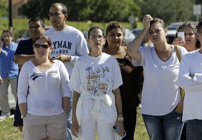 FILE – This Nov. 10, 2010, file photo shows parents waiting to pick up their children at Lakeside Elementary School in Pembroke Pines, Fla., after authorities lifted a lockdown of all schools in Broward County. The threatening comments of a Florida woman about