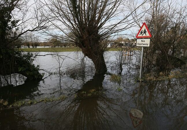 In this photo taken Sunday Feb. 2, 2014, A road sign telling drivers to take care of pedestrians is seen on the flooded road between Langport and Muchelney in Somerset, England, the village has been cut off by road since Jan. 1 this year. Here on the Somerset Levels _ a flat, marshy region of farmland dotted with villages and scored by rivers and ditches _ it's often wet. But not this wet. Thousands of acres of this corner of southwest England have been under water for weeks, some villages have been cut off for more than a month, and local people forced to take boats to get to school, work and shops are frustrated and angry. Some blame government budget cuts and environmental bureaucracy. Others point to climate change. Even plump, endangered water voles are the target of ire. (AP Photo/Alastair Grant)