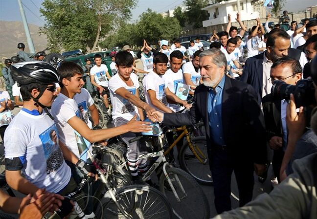 Afghan youth supporters shake hands with presidential candidate Abdullah Abdullah before a cycling event in Kabul, Afghanistan, Friday, June 6, 2014, shortly before two blasts struck a convoy carrying Abdullah following another campaign event, killing several civilians but leaving the candidate himself unharmed. (AP Photo/Rahmat Gul)