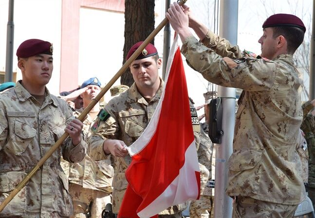 Master Cpl. Daniel Choong (left), Cpl. Harry Smiley (centre) and Cpl . Gavin Early (right) take down the Canadian flag for the last time in Afghanistan on Wednesday March 12, 2014, bringing an end to 12 years of military involvement in a campaign that cost the lives of 158 soldiers. THE CANADIAN PRESS/Murray Brewster