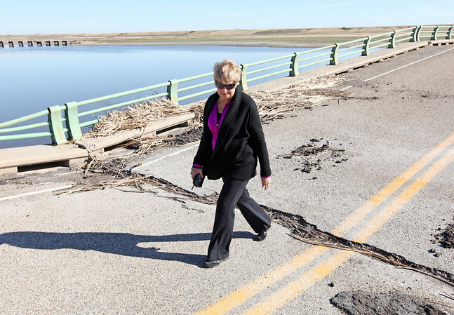 In this September 2011 photo, Betty Miller crosses the washed-out Highway 251 bridge over the Souris River east of Coulter following a rally near the structure. Miller was among a group of area residents, farmers and workers who called on various levels of government to replace the bridge after it collapsed due to flooding in spring 2011.