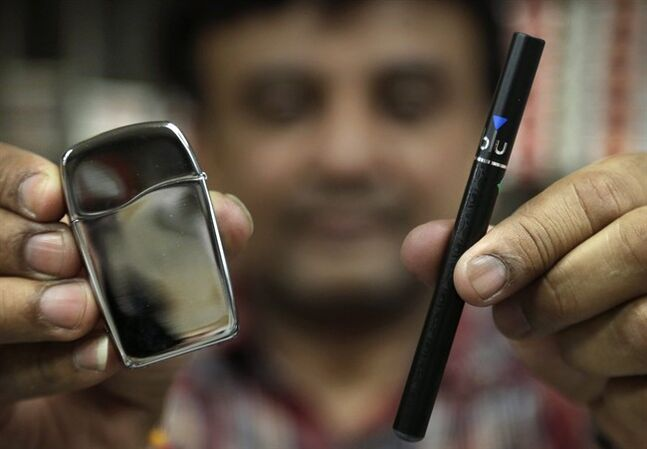 Sales clerk Sam Patel, of Waltham, Mass., displays Zippo Blu butane lighter, left, and a blu e-cigarette, right, at a shop, Wednesday, May 21, 2014, in Brookline, Mass. The maker of Zippo lighters and Lorillard, the nation's third-biggest tobacco company, are battling over the Blu brand name being used on both Zippo lighters and an electronic cigarette brand. (AP Photo/Steven Senne)