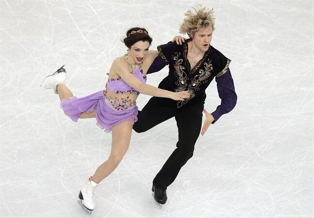 FILE - In this Feb. 17, 2014, file photo, Meryl Davis and Charlie White, right, compete in the ice dance free dance figure skating finals at the Iceberg Skating Palace during the 2014 Winter Olympics in Sochi, Russia. Four months after winning at the Sochi Olympics, the Michigan natives announced Friday, June 6, 2014, that they will skip the 2014-15 season. (AP Photo/Ivan Sekretarev, File)
