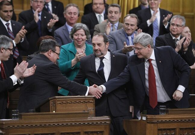 Prime Minister Stephen Harper (right) shakes hands with Finance Minister Jim Flaherty after he tabled the federal budget in the House of Commons on Parliament Hill in Ottawa on Tuesday, February 11, 2014. THE CANADIAN PRESS/Fred Chartrand