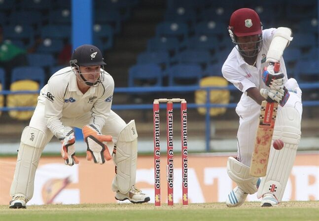 West Indies batsman Kraigg Brathwaite, right, defends his wicket as New Zealand's wicket keeper BJ Watling, left, watches during the second day of their second cricket Test match in Port of Spain, Trinidad, Tuesday, June 17, 2014. (AP Photo/Arnulfo Franco)