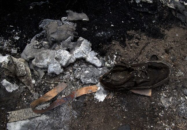 A shoe lies next to melted aluminum at the crash site of Malaysia Airlines Flight 17 near the village of Hrabove, eastern Ukraine, Tuesday, July 22, 2014. A team of Malaysian investigators visited the site along with members of the OSCE mission in Ukraine for the first time since the air crash last week.(AP Photo/Vadim Ghirda)