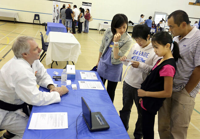 Sharon Huang, centre, an interpreter with Westman Immigrant Services, chats with mother Xiaju Chuan, daughter Huiya Qian and father Junwei Yu as they get information on karate classes from instructor Richard Wharf at Assiniboine Community College on Saturday. The group was taking part in the Newcomers Physical Activity Expo, which offered recent immigrants information on outlets for physical fitness in Brandon.