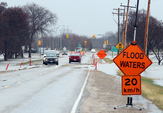 Floodwater from the swollen Assiniboine River begins to overlap a portion of Grand Valley Road just west of 18th Street in Brandon on Sunday afternoon.