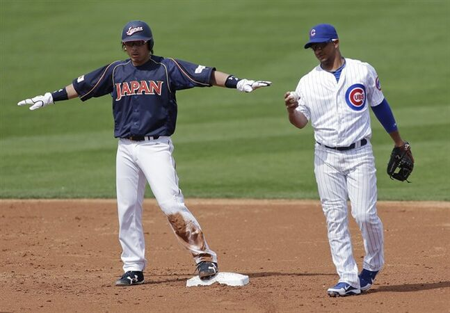 Japan's Nobuhiro Matsuda, left, celebrates after stealing second as Chicago Cubs second baseman Alberto Gonzalez looks at the ball during the second inning of a spring training baseball game in Mesa, Ariz. Friday, March 15, 2013. (AP Photo/Chris Carlson)
