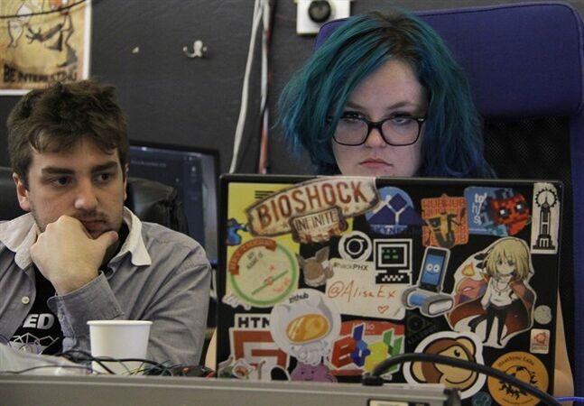 Brett Warner, left, watches as Alisa Palson works on a project at HeatSync Labs in Phoenix, in this photo made Sunday, July 27, 2014. Palson, 22, started coming to HeatSync to make clothing and accessories that mimic characters from movies and video games for conferences she attended. The nondescript garage-like workshop nestled between restaurants, a flower shop and jewelry stores offers a space where inventors and tinkerers can work on projects and share ideas. (AP Photo/Emaun Kashfi)