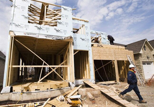 Construction workers build a new home in Oakville, Ont., on April 14, 2009. THE CANADIAN PRESS/Nathan Denette