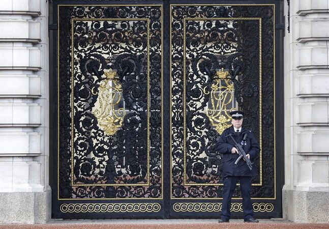 An armed police officer stands at the gates inside the grounds of Buckingham Palace in London, Tuesday, Jan. 28, 2014. British lawmakers have criticised the financial affairs of Queen Elizabeth II and her household, urging the monarch to bring in more income by opening up Buckingham Palace to visitors more often. (AP Photo/Kirsty Wigglesworth)
