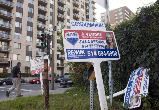 A real estate signs stand in front of a condominium September 27, 2011 in Montreal. THE CANADIAN PRESS/Ryan Remiorz