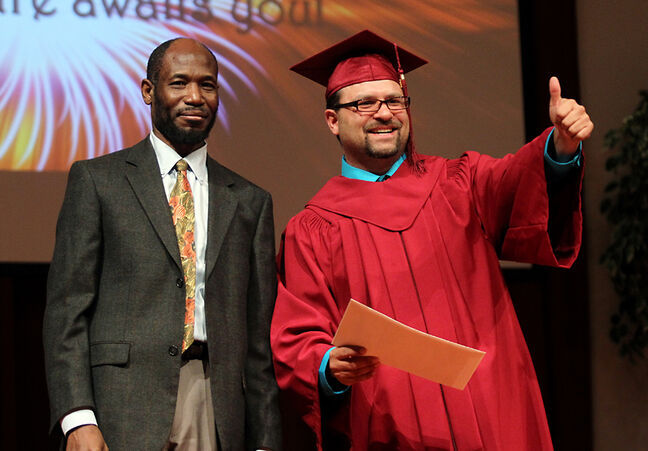 Ryan David Dubreuil gives a thumbs up to the crowd while receiving his diploma from Akapelwa Mweemba, the acting director of ACC's Adult Collegiate, on Saturday.