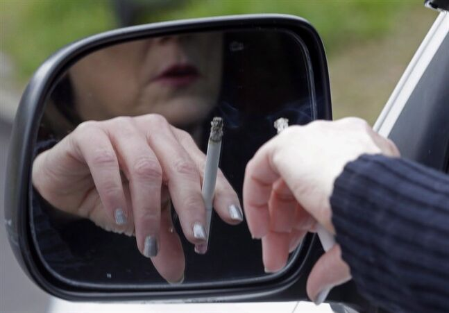 A woman smokes a cigarette while sitting in her truck in Hayneville, Ala., on March 2, 2013. Nearly a third of hospital bed usage in Ontario between 2001 to 2012 was attributable to health problems induced by unhealthy behaviours - smoking, excess drinking, poor diet and physical inactivity - a new report suggests. THE CANADIAN PRESS/AP, Dave Martin