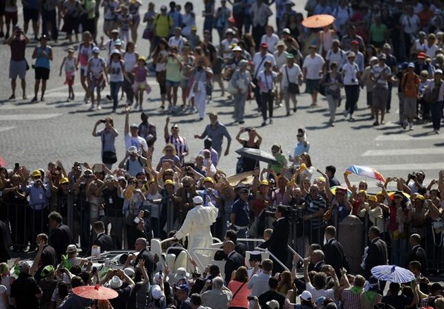 Poeple gather to see Pope Francis drive by during his weekly general audience in St. Peter's Square at the Vatican, Wednesday, June 11, 2014. (AP Photo/Gregorio Borgia)