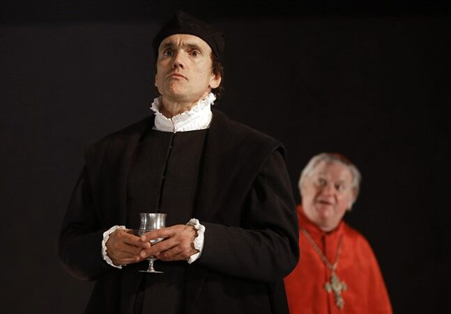 In this Thursday, May 15, 2014 photo, a scene from 'Wolf Hall' with Ben Miles as Thomas Cromwell, foreground, and Paul Jesson as Cardinal Wolsey, right, during a media opportunity at the Aldwych Theatre in London. Hilary Mantel's Booker Prize-winning best-seller about deadly intrigue at the court of King Henry VIII will soon be a BBC series with Tony Award-winner Mark Rylance and