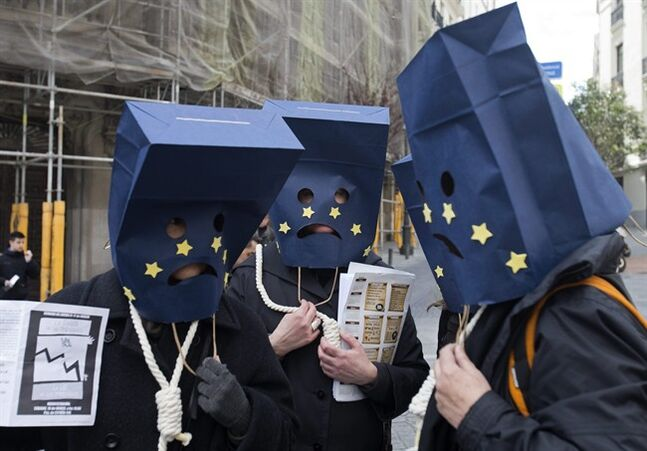 Protesters pose as they wear EU bags over their heads and nooses around their necks protest as the 'Stop Evictions platform' held a press conference in the street outside the Spanish parliament in Madrid, Spain, Thursday March 14, 2013. The European Court of Justice in Luxembourg has ruled Thursday March 14, 2013, that harsh property repossession laws in Spain violate EU laws on consumer protection. Hundreds of thousands of evictions have taken place during Spain's deep recession, but the watershed ruling said Spanish legislation infringes EU law as it does not allow courts to halt eviction orders on the basis of possible unfair terms in mortgage agreements. (AP Photo/Paul White)