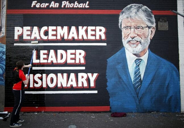 A man adds the finishing touch to a newly painted mural of Gerry Adams on the Falls Road, West Belfast, Northern Ireland, Northern Ireland, Friday, May, 2 2014. Police continue to question the Sinn Fein leader Gerry Adams at Antrim police station about the 1972 murder of Jean McConville. (AP Photo/Peter Morrison)