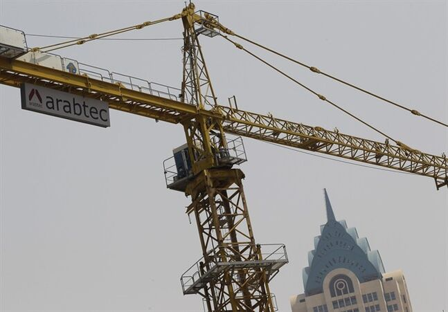 A worker operates a crane of the Arabtec construction company on a high-rise building in Dubai, United Arab Emirates, Wednesday, July 2, 2014. The chairman of Arabtec, the embattled Dubai construction firm that helped build the world's tallest tower, promised Wednesday to improve transparency at the firm and said it retains the support of a major shareholder backed by the Abu Dhabi government. (AP Photo/Kamran Jebreili)
