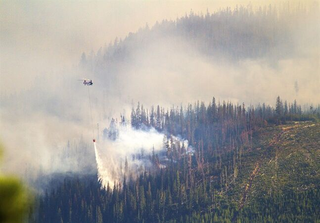 A helicopter dumps a load of water onto one of the fires burning on a ridge west of Leavenworth, Wash., Thursday, July 17, 2014. The fire chased people from nearly 900 homes as it burned near the Bavarian-themed village of Leavenworth. The Chiwaukum Creek Fire sent a light dusting of ash over Leavenworth, where the German-style motif provides a backdrop to Oktoberfest and a Christmas tree lighting festival. (AP Photo/The Seattle Times, Mike Siegel)