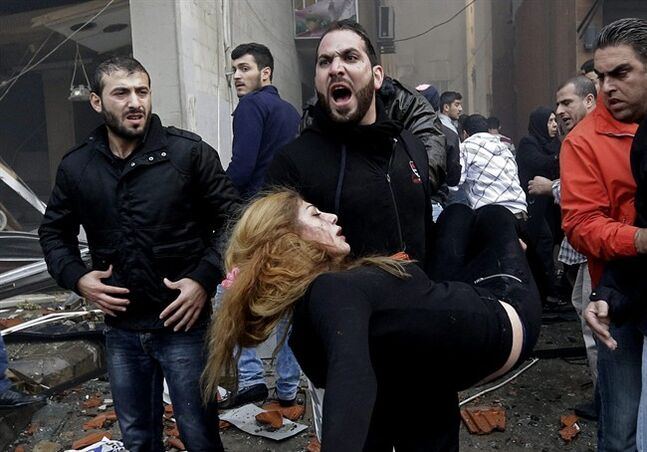A Lebanese man carries an injured woman away from the site of a car bomb explosion in a Shiite area and stronghold of the Lebanese militant group Hezbollah at the southern suburb of Beirut, Thursday Jan. 2, 2014. A large explosion has rocked a stronghold of the Shiite Hezbollah group in the southern suburbs of the Lebanese capital. (AP Photo/Hussein Malla)
