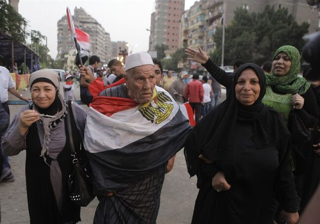 An elderly Egyptian voter covers himself with a national flag as he walks with his family outside a polling center during the second day of voting in the presidential election, in Cairo, Egypt, Tuesday, May 27, 2014. Egypt extended its presidential election an extra day after two days of reportedly low voter turnout, an embarrassment to attempts by the front-runner, former army chief Abdel-Fattah el-Sissi, to garner an overwhelming show of public support. Opponents and observers call the thin voting a warning, showing the extent of discontent with the sure winner despite months of media frenzy depicting him as the nation's savior for ousting the Islamist president. (AP Photo/Amr Nabil)
