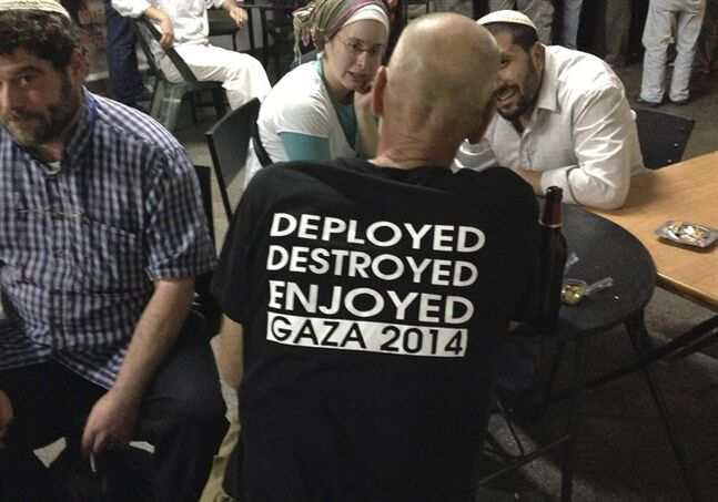 An Israeli army reservist officer, back on camera, wearing a T-shirt referring to the Israeli forces' operations during the war in Gaza, talks with others outside a bar in Jerusalem, early Wednesday, Aug. 13, 2014. Egypt presented a proposed cease-fire to Israel and Hamas aimed at ending the monthlong war, Palestinian officials said early Wednesday after negotiators huddled for a second day of Egyptian-mediated talks meant to resolve the crisis and bring relief to the embattled Gaza Strip. (AP Photo/Lefteris Pitarakis)