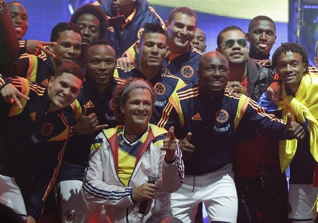 FILE - In this May 23, 2014 file photo, Colombia's singer Carlos Vives, front row, center, poses with Colombia's national soccer team after singing at their send-off exhibition game at El Campin stadium in Bogota, Colombia. Colombia had extra motivation in winning its first game in the World Cup this weekend: 200 of the players' family members attended the big event. Colombia beat Greece 3-0 on Saturday, June 14, 2014, and their presence was strong since Grammy-winning singer Vives partnered with Toronto-based oil company Pacific Rubiales Energy Corp. to send players' family members who couldn't afford to pay the costs of the trip to the World Cup. (AP Photo/Ricardo Mazalan, File)