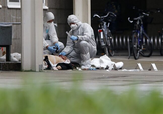 EDS NOTE GRAPHIC CONTENT - Criminal experts examine the body of a person killed in front of a court in Frankfurt, Germany, Friday, Jan. 24, 2014. Two people were killed in a shooting and knife stabbing. (AP Photo/Michael Probst)