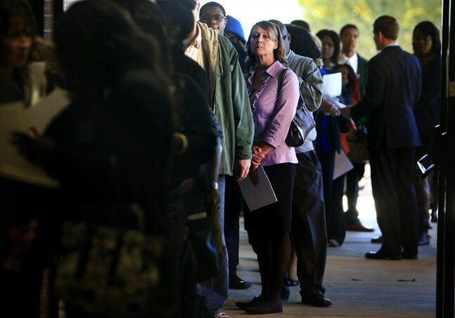 FILE - In this Nov. 7, 2013 file photo, Jona Caldwell joins a long line of job seekers outside the Ferguson Community Center in Cordova, Tenn. The Labor Department reports on the number of Americans who applied for unemployment benefits in the last week on Dec. 26, 2013. (AP Photo/The Commercial Appeal, Jim Weber, File)