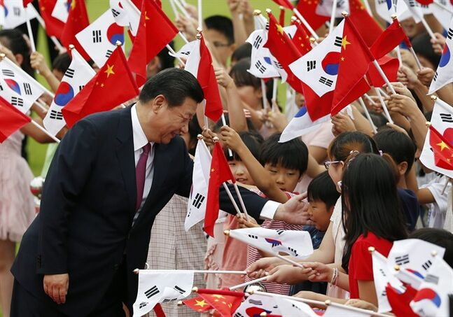 Chinese President Xi Jinping greets children during a welcome ceremony at the Presidential Blue House in Seoul, South Korea, Thursday, July 3, 2014. Xi's choice to meet with South Korean President Park Geun-hye over North Korean leader Kim Jong Un upends the practice since Beijing and Seoul forged diplomatic ties in 1992 of Chinese presidents choosing to make Pyongyang their first official destination on the Korean Peninsula. (AP Photo/Kim Hong-ji, Pool)