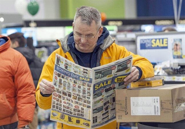 A customer reads a flyer at a retail store in Ottawa on Dec. 26, 2013. THE CANADIAN PRESS/Justin Tang